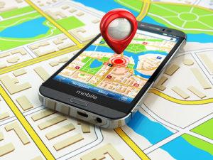 illustrazione di un cellulare con un puntatore gps adagiato su di una cartina